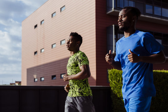 Ethnic men jogging together on street