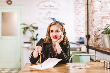 Young lady in leather jacket sitting at the table with notebook and pencil in hand and joyfully looking aside while spending time in cafe