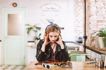 Young pensive lady in leather jacket sitting and thoughtfully lookig at many different sunglasses on table in cafe