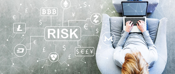 Cryptocurrency Risk Theme with man using a laptop in a modern gray chair