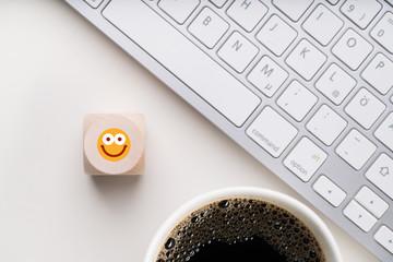 sehr waches Smiley auf Würfel am Arbeitsplatz