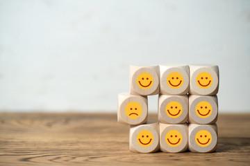 Viele Würfel mit lächelnden Smileys und einer der unzufrieden ist