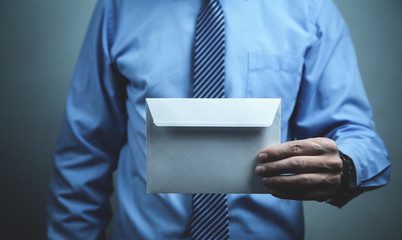 Businessman holding blank mail envelope. Business concept