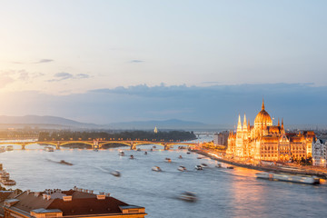 Aerial cityscape view with motion blurred ships and illuminated Parliament building during the twilight in Budapest, Hungary