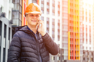 young handsome man builder in an orange helmet talking on the phone on the background of a building under construction