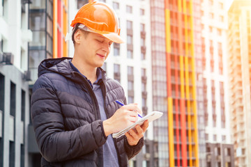 young handsome man builder in an orange helmet writes in a notebook on the background of a building under construction