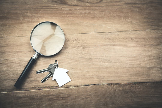 Magnifying glass with house and key on wooden background.