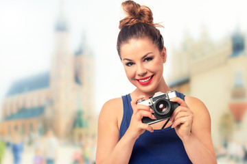 Vacation photographer concept - beautiful and attractive woman holding a retro SLR camera and smiling on blurred background of a historic city (vintage effect).