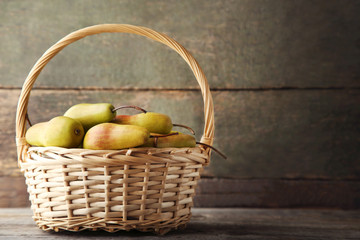 Ripe and sweet pears in basket on grey wooden table