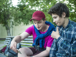 two young handsome guys checking news feed in social network outdoors on a summer day in park