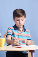 Caucasian boy drawing with colorful pencils.