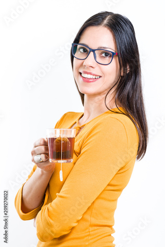 896a482d37db6f Beautiful brunette woman holding transparent cup with tea bag looking at  the camera - white background