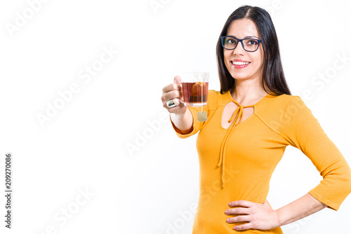5fac86ae878ed6 Beautiful brunette woman showing transparent cup with tea bag looking at  camera - white background