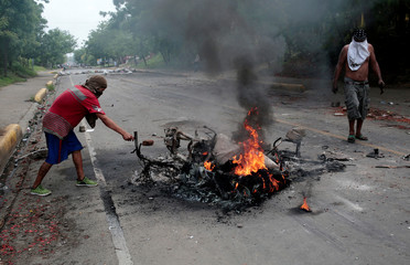 Protester stand next to a burned motorcycle during a protest against Nicaragua's President Daniel Ortega's government in Tipitapa
