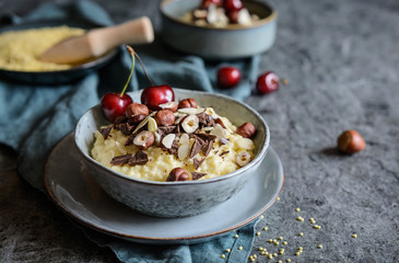 Millet porridge topped with chocolate pieces, hazelnuts, almond slices and cherry