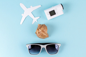Sea shell, action camera, airplane and sunglasses on a blue background. Vacation concept. Copy space.