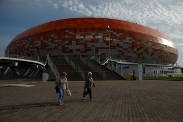 Women walk past the Mordovia Arena in Saransk