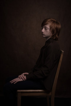 Studio portrait profile of redhead boy sitting on chair in classic rembrandt painterly style