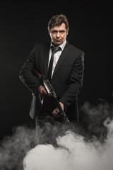 Handsome middle aged man gangster with Thompson machine gun on dark background