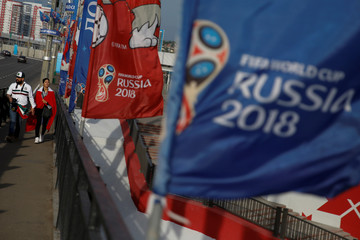 Fans walk next to promotional flags of the 2018 FIFA World Cup close to the Mordovia Arena in Saransk