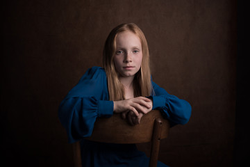 Studio portrait of girl sitting on chair