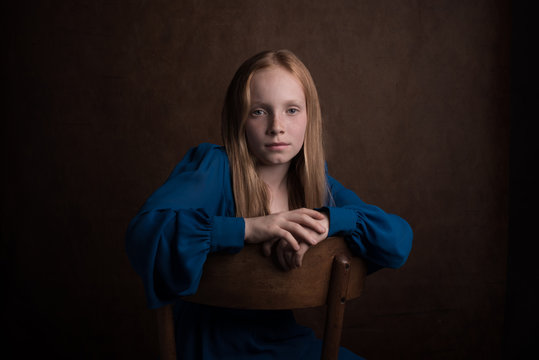 Classic studio portrait of girl in blue dress sitting on chair
