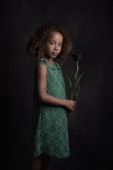Studio portrait of girl holding flower