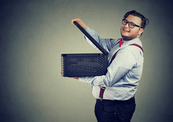 Cheerful chunky man opening a box