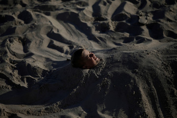 A boy smiles after being buried on the beach in the Black Sea resort of Sochi