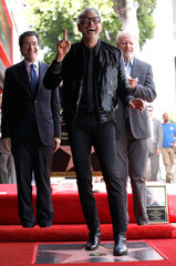 Actor Goldblum poses on his star, as Eisen and Begley Jr. watch, after it was unveiled on the Hollywood Walk of Fame in Los Angeles