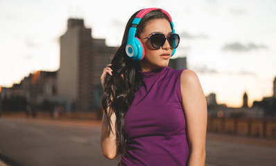 Young girl listening music in headphones in the city