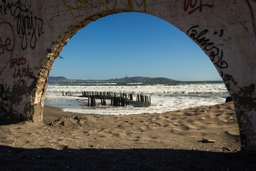 Arc of ruined fortress in La Serena with views of Coquimbo city on the background, Chile. Abandoned building by the beach
