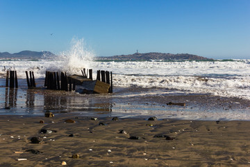 Wild waves hitting on wooden pillars of jetty in La Serena beach with views of Coquimbo city on the background, Chile. Climate change concept