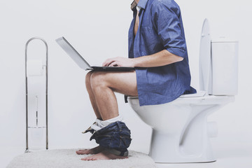 Man is working with laptop while sitting on toilet.
