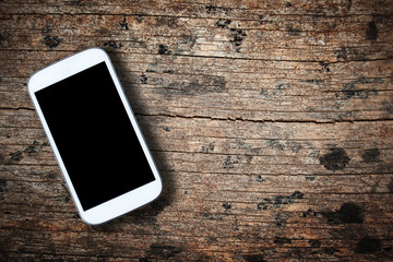 Smartphone on old wooden table background