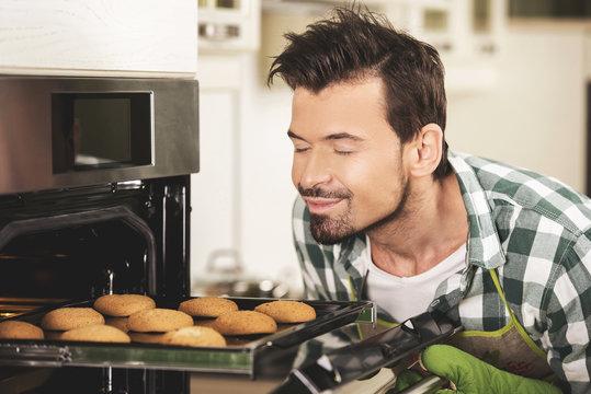 Smiling man sniffing cookies.