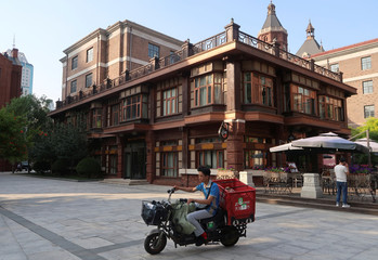 A delivery driver rides past a western style building in central Tianjin