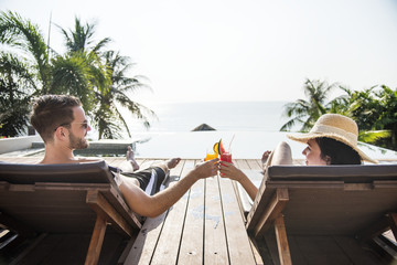 Couple toasting with cocktails by the pool