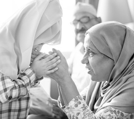 Muslim girl paying respect to mother