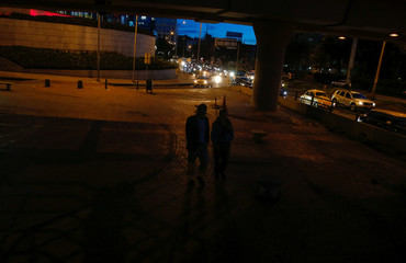 People walk under a viaduct in Bogota city
