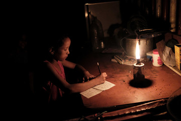 A girl writes next to a candlelight outside her house in the countryside of Tolima,