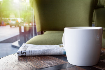 White Cup of coffee with newspaper on the wooden table, street and car background.