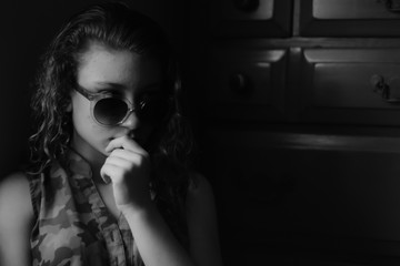 Young girl looking serious with sunglasses on