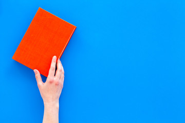 Reading for leasure. Hands take hardback book with empty cover on blue background top view space for text