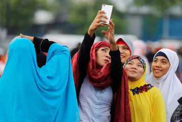 Filipino Muslims take a selfie during the first day celebration of Eid al Fitr before morning prayers at Luneta Park in Manila