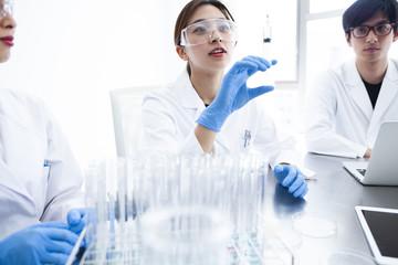 実験用注射器をもつ女性研究員と研究室