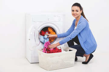 Young woman loading clothes in washing machine.