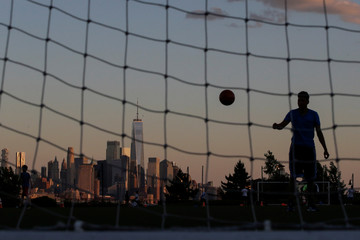 People play soccer at the waterfront park and recreation center while the One World Trade Center and Lower Manhattan in New York are seen at the background from Weehawken, New Jersey