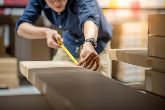 Young Asian man using tape measure for measuring dimension of product in cardboard box. Shopping lifestyle in warehouse concept