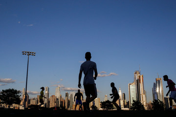 People play soccer at the waterfront park and recreation center while the Empire State Building and Middle Manhattan in New York are seen from Weehawken, New Jersey